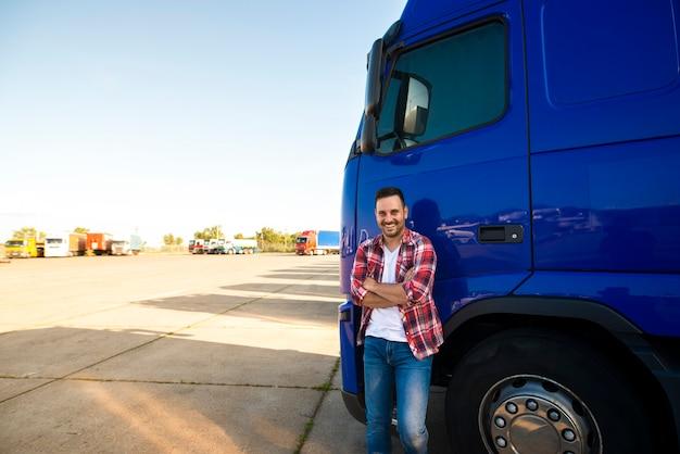 Portret uśmiechnięty trucker stojący przy jego ciężarówce gotowy do jazdy