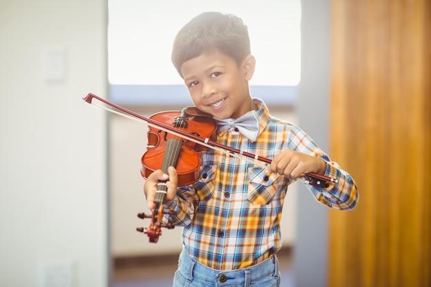 Portret uśmiechnięty uczeń bawić się skrzypce w sala lekcyjnej