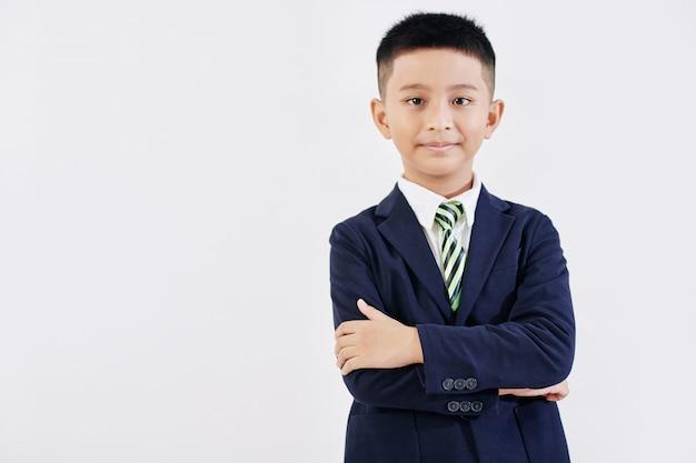 Portret uśmiechnięty uczeń pewnie w szkolnym mundurku, składając ramiona i patrząc na kamery