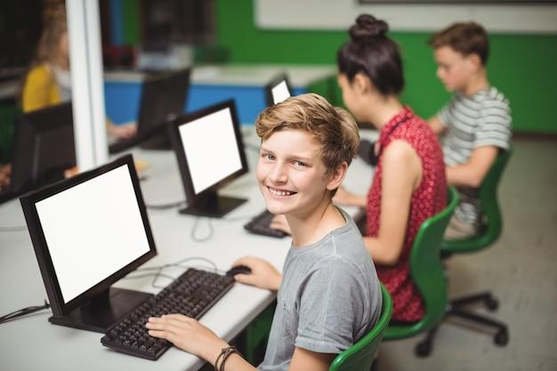 Portret uśmiechnięty uczeń studiuje w sali komputerowej
