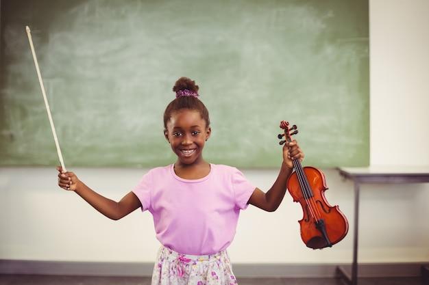 Portret uśmiechnięty uczennicy mienia skrzypce w sala lekcyjnej