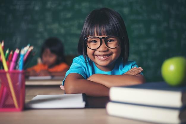 Portret uśmiechnięty uczennicy obsiadanie przy stołem z książkami
