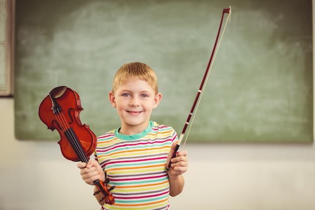 Portret uśmiechnięty uczniowski mienie skrzypce w sala lekcyjnej