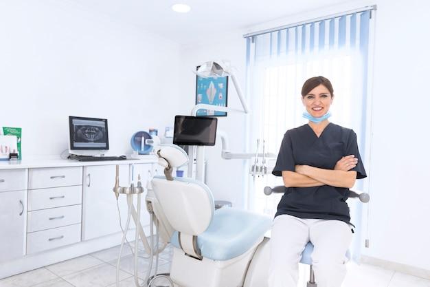 Portret uśmiechnięty ufny dentysta w klinice z maszyną i wyposażeniem
