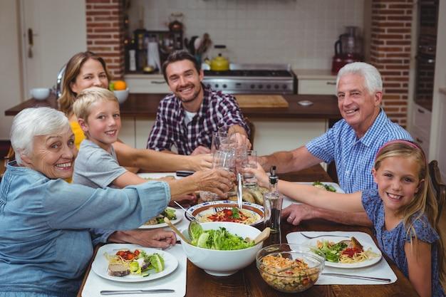 Portret uśmiechnięty wielopokoleniowy rodzinny wznosi toast napój