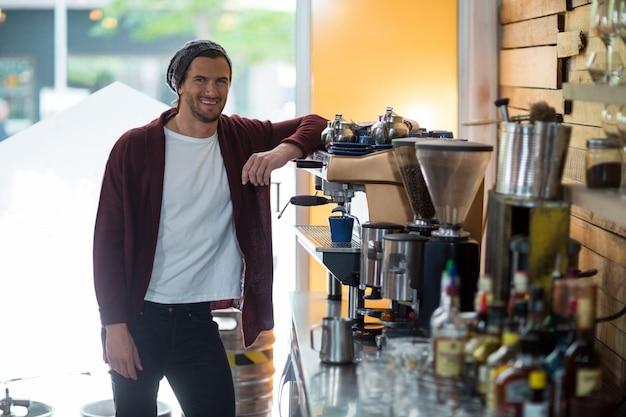 Portret uśmiechnięty właściciel stoi blisko kawy espresso maszyny