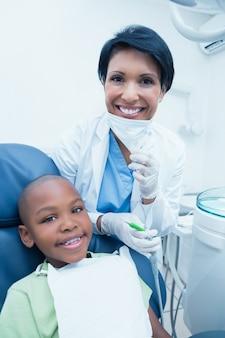 Portret uśmiechnięty żeński dentysta egzamininuje chłopiec zęby