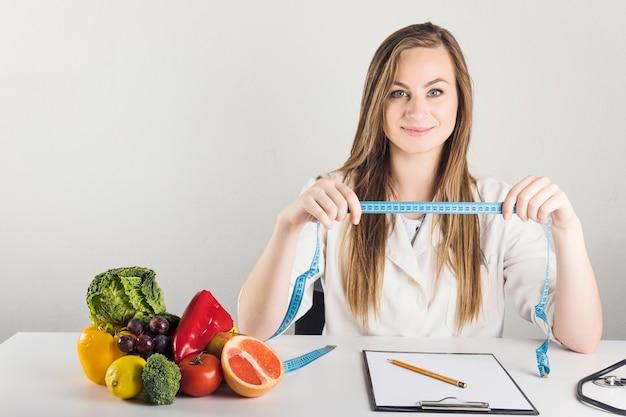 Portret uśmiechnięty żeński dietician trzyma pomiarowej taśmy