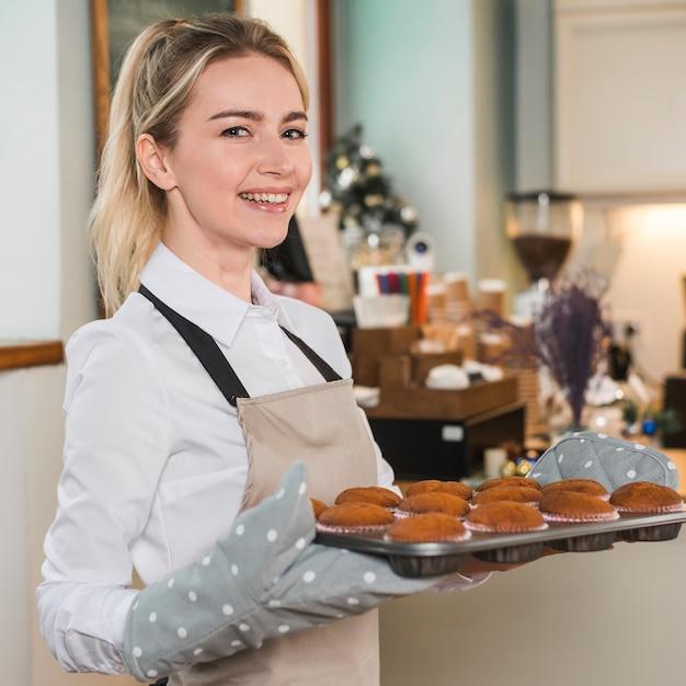 Portret uśmiechnięty żeński piekarz jest ubranym mitenki mienie piec muffins w tacy