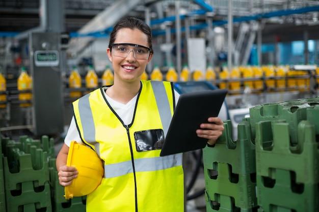 Portret uśmiechnięty żeński pracownik używa cyfrową pastylkę