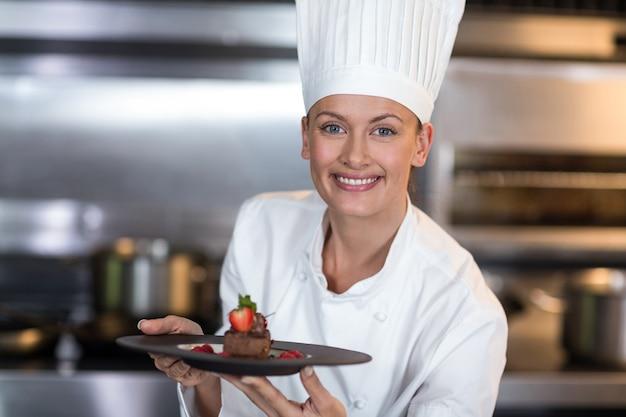 Portret uśmiechnięty żeński szefa kuchni mienia talerz