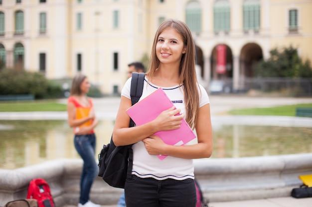 Portret uśmiechnięty żeński uczeń przed jej szkołą wyższa