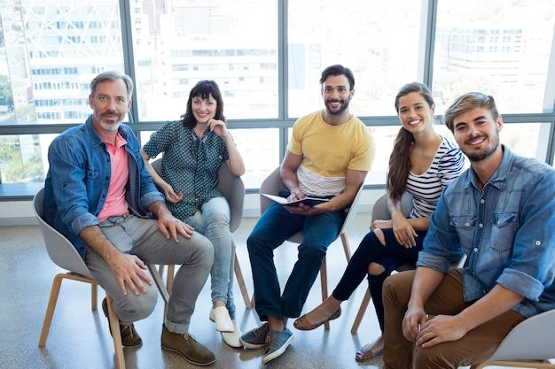 Portret uśmiechnięty zespół kreatywnych biznes siedzi razem w biurze