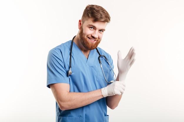Portret uśmiechnięty życzliwy doktorski kładzenie na bezpłodnych rękawiczkach