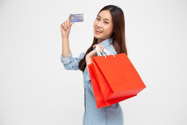 Portret uśmiechniętych azjatyckich kobiet w niebieskiej dżinsowej koszuli z kartą kredytową i czerwoną torbą na zakupy na białym tle nad białą ścianą, młoda kobieta, szczęśliwy poczucie kupującego