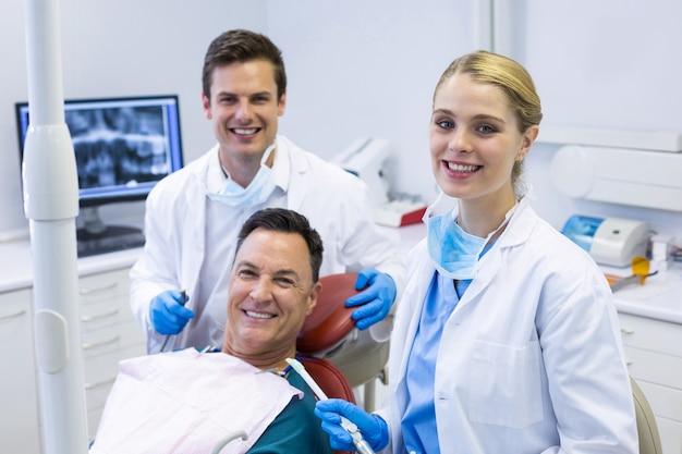 Portret uśmiechniętych dentystów i pacjenta płci męskiej