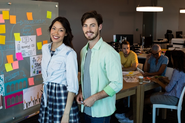 Portret uśmiechniętych kreatywnych ludzi biznesu stojących w biurze