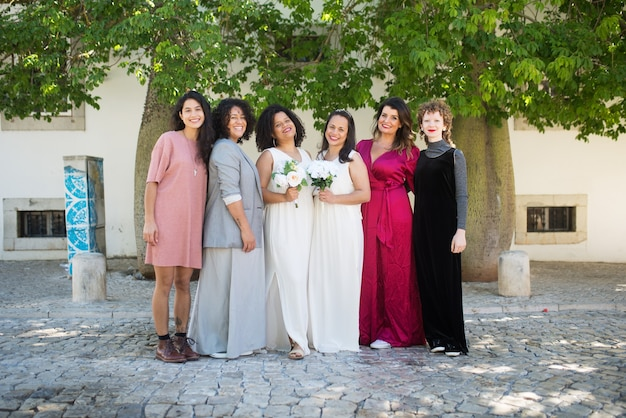 Portret uśmiechniętych narzeczonych i gości na weselu. kobiety różnych narodowości w odświętnych strojach stoją razem