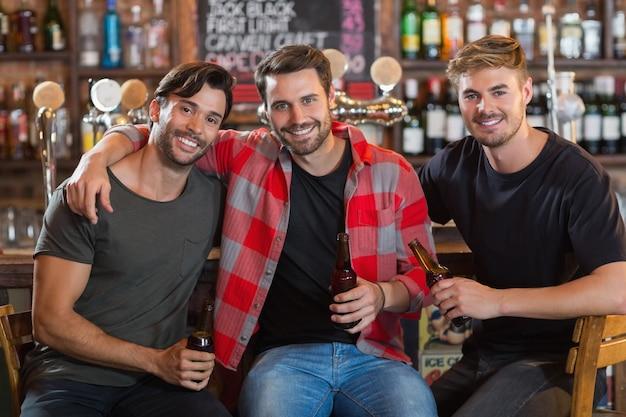 Portret uśmiechniętych przyjaciół płci męskiej trzymając butelki piwa w barze
