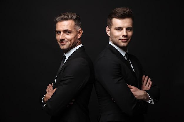 Portret uśmiechniętych przystojnych dwóch biznesmenów ubranych w formalny garnitur, pozujących do kamery plecami do siebie na białym tle nad czarną ścianą