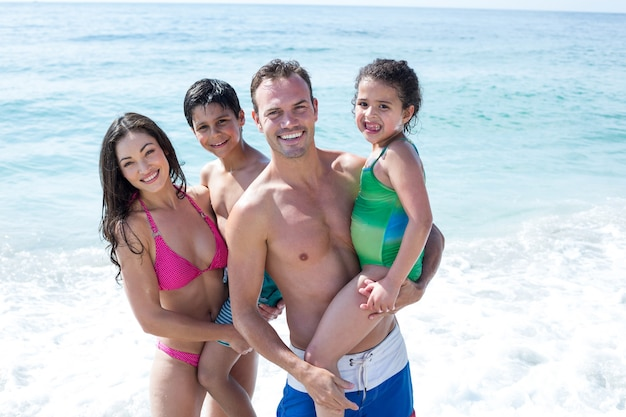 Portret uśmiechniętych rodziców z dziećmi na plaży