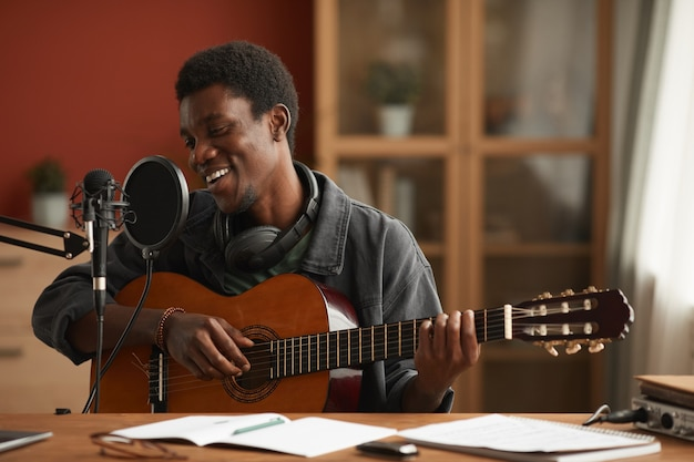 Portret utalentowanego mężczyzny afroamerykańskiego śpiewającego do mikrofonu i gry na gitarze podczas nagrywania muzyki w studio, kopia przestrzeń
