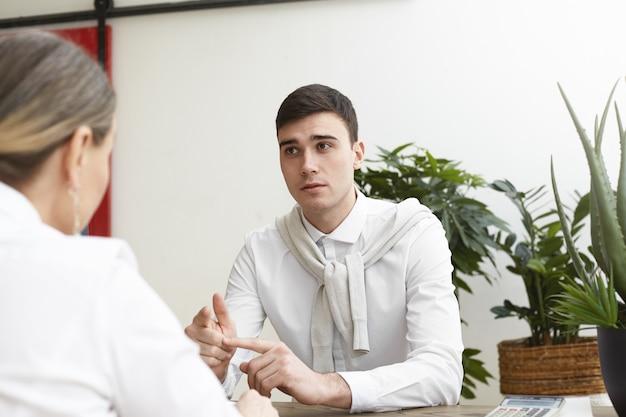 Portret utalentowanego, zręcznego młodego mężczyzny ubiegającego się o pracę, który ma spotkanie z kobietą rekrutującą podczas ubiegania się o stanowisko projektanta w dużej firmie, liczy palce, wymieniając jego mocne strony