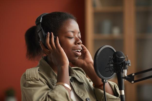 Portret utalentowanej kobiety afroamerykańskiej śpiewającej do mikrofonu i noszącej słuchawki podczas nagrywania muzyki w studio, kopia przestrzeń