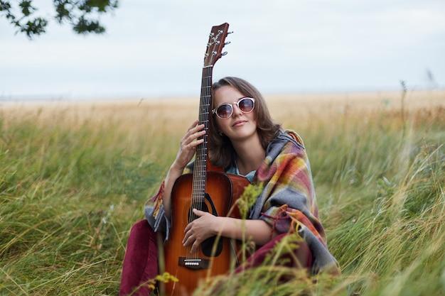 Portret utalentowany żeński muzyk siedzi przy zieloną trawą z gitarą ma rozważnego wyrażenie podziwia naturę jest samotnie