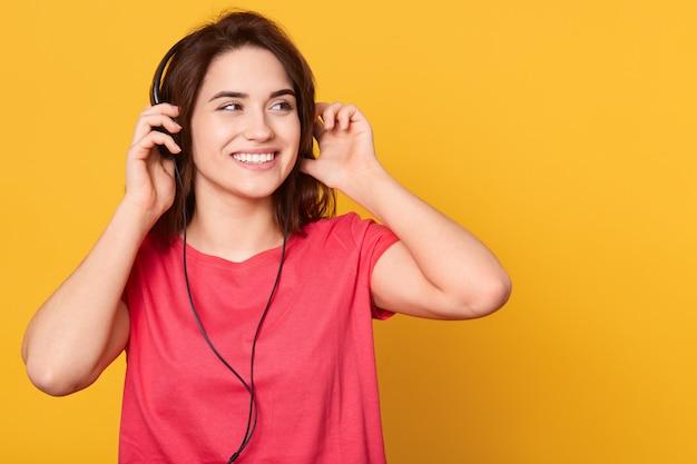 Portret utrzymuje ręce na hełmofonach piękna młoda kobieta