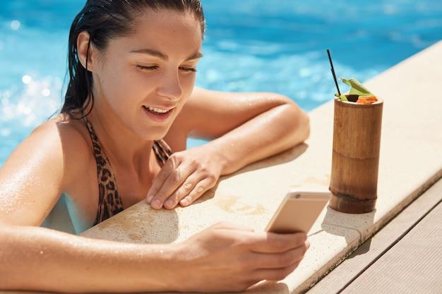 Portret uważna piękna kobieta jest w czystym pływackim basenie