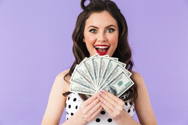 Portret uwodzicielskiej kobiety pin-up w klasycznej sukience w kropki uśmiecha się, trzymając kilka banknotów na białym tle nad fioletową ścianą