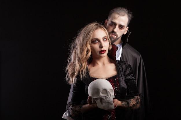 Portret uwodzicielskiej pary przebranej jak wampiry na karnawał na halloween. mężczyzna w stroju drakuli. sexy wampir kobieta trzyma ludzką czaszkę.