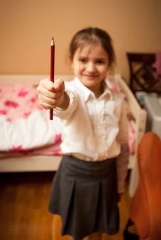 Portret w domu małej uczennicy trzymającej czerwony ołówek