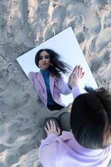 Portret w lustrze pięknej dziewczyny na tle nieba