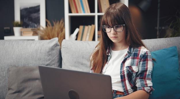 Portret w pasie skoncentrowana nastolatka studiuje na laptopie siedząc na kanapie w domu, widok z przodu