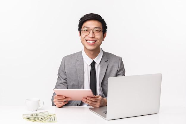 Portret w pasie wesoły, szczęśliwy uśmiechnięty azjatycki pracownik biurowy w garniturze, siedzący przy stole studiujący wykres za pomocą cyfrowego tabletu i laptopa, odbierający połączenia za pomocą bezprzewodowych słuchawek, na białej ścianie