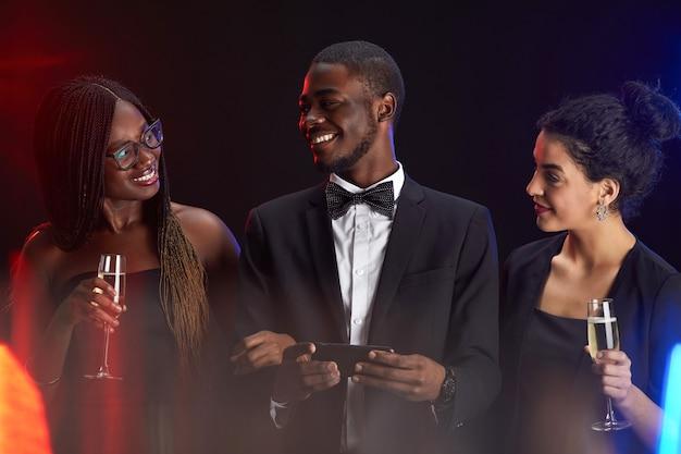 Portret w pasie wieloetnicznej grupy przyjaciół, uśmiechając się radośnie podczas eleganckiej imprezy