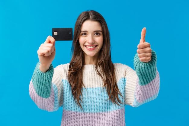 Portret w pasie zadowolona młoda kobieta z uśmiechem poleca bank, otrzymała stypendium, pokazuje kciuk, kartę kredytową, zgodę na skinienie głowy i umowę, jak nowe funkcje, cashback, niebieska ściana