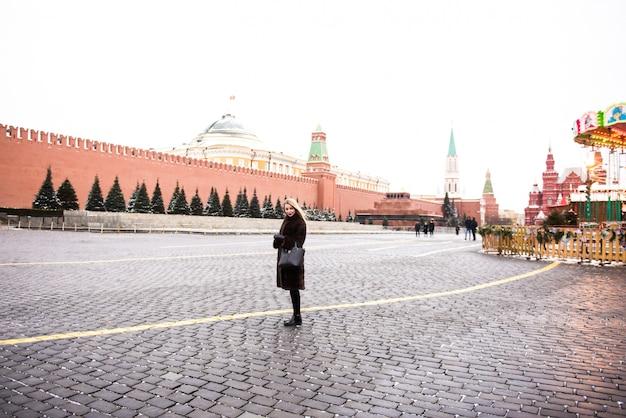 Portret w pełni wzrostu, piękna rosjanka w płaszczu z norek na placu czerwonym w moskwie w czasie świąt bożego narodzenia