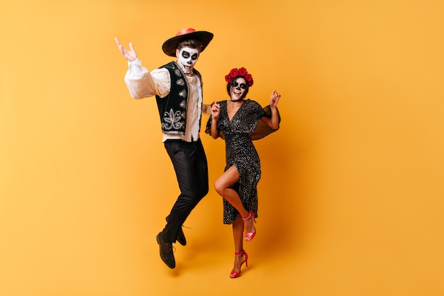 Portret w pełnym rozkwicie tańczących śmiesznych mężczyzn i jego słodkiej damy. dziewczyna w koronie róż i pomalowanej twarzy bawi się halloween ze swoim chłopakiem.