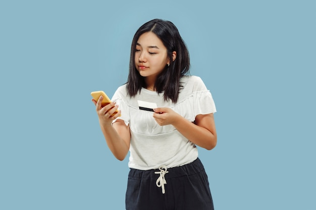 Portret w połowie długości koreański młodej kobiety na niebieskiej przestrzeni. modelka używa swojego smartfona do płacenia rachunków lub zakupów online.