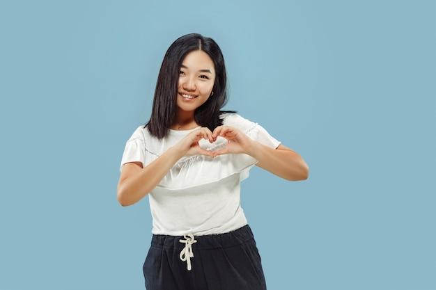 Portret w połowie długości koreański młodej kobiety na niebieskiej przestrzeni. modelka w białej koszuli. pokazuje znak serca.