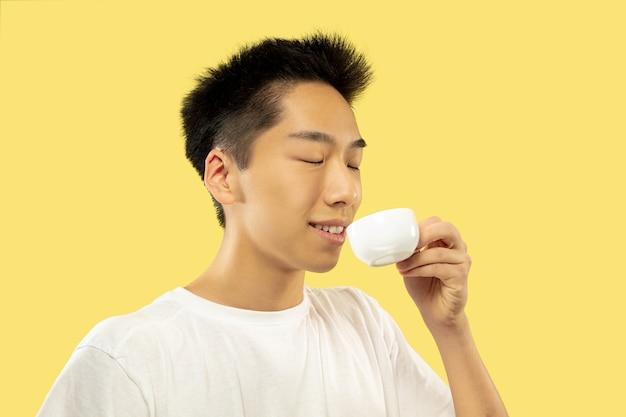 Portret w połowie długości koreański młody człowiek na żółto