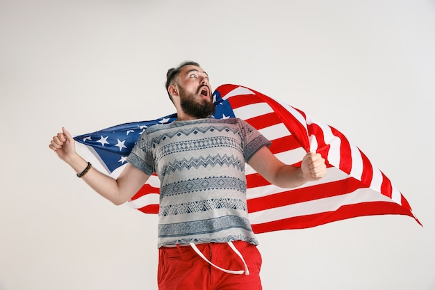 Portret w połowie długości młody człowiek z flagą usa na białym tle na białym studio.