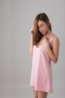 Portret w połowie długości, piękna azjatka w różowej sukience stojąca na szaro; śliczna modelka pozuje w studiu; copyspace.
