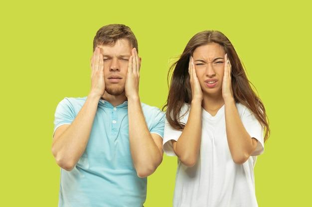 Portret w połowie długości pięknej młodej pary na białym tle. kobieta i mężczyzna cierpią na bóle głowy lub złe wieści. wyraz twarzy, koncepcja ludzkich emocji.