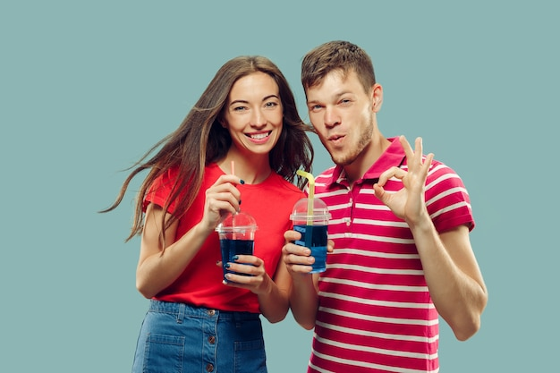 Portret w połowie długości pięknej młodej pary na białym tle. kobieta i mężczyzna stojący z napojami, uśmiechając się i podpisując ok. wyraz twarzy, koncepcja lato, weekend. modne kolory.