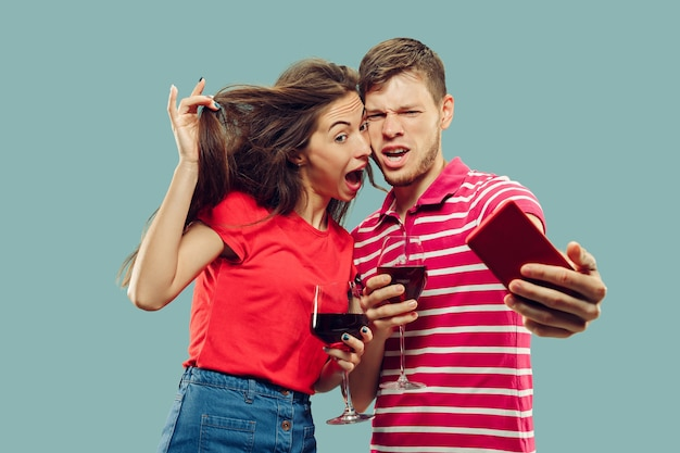 Portret w połowie długości pięknej młodej pary na białym tle. uśmiechnięta kobieta i mężczyzna trzyma kieliszki z winem i robi selfie. wyraz twarzy, koncepcja lato, weekend.