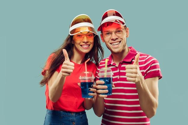 Portret w połowie długości pięknej młodej pary na białym tle. uśmiechnięta kobieta i mężczyzna w czapkach i okularach przeciwsłonecznych z napojami. wyraz twarzy, koncepcja lato, weekend. modne kolory.